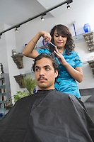 Hairdresser cutting mans hair