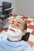 Man with shaving foam on face at barbers