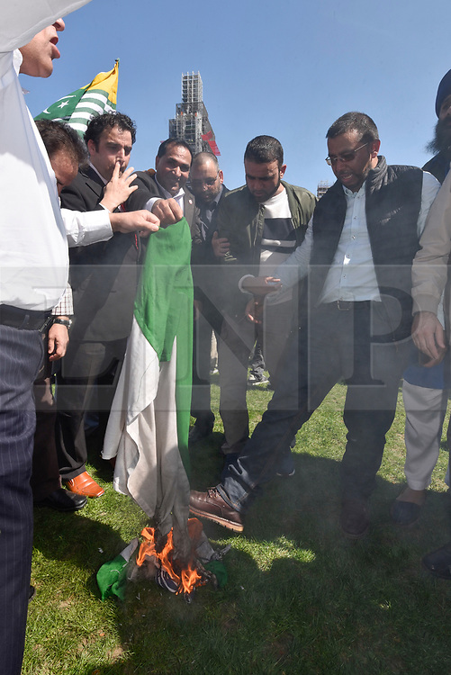 © Licensed to London News Pictures. 18/04/2018. LONDON, UK. Kashmiri and Sikh demonstrators set fire to the Indian flag in Parliament Square in protest against the regime of Indian Prime Minister Narendra Modi.  Sikhs, Kashmiri muslims and other groups all had their own message against PM Modi who is visiting London to take part in the Commonwealth Heads of Government 2018 summit. Parliament Square has been decorated with flags of countries of the Commonwealth. Photo credit: Stephen Chung/LNP