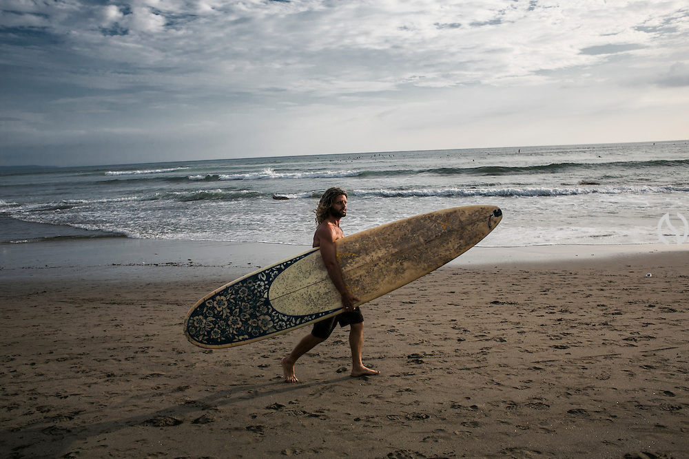 BALI, INDONESIA; APRIL 17, 2015: A surfer carries his surf board at Batubolong beach, Bali, Indonesia on Friday April 17, 2015.