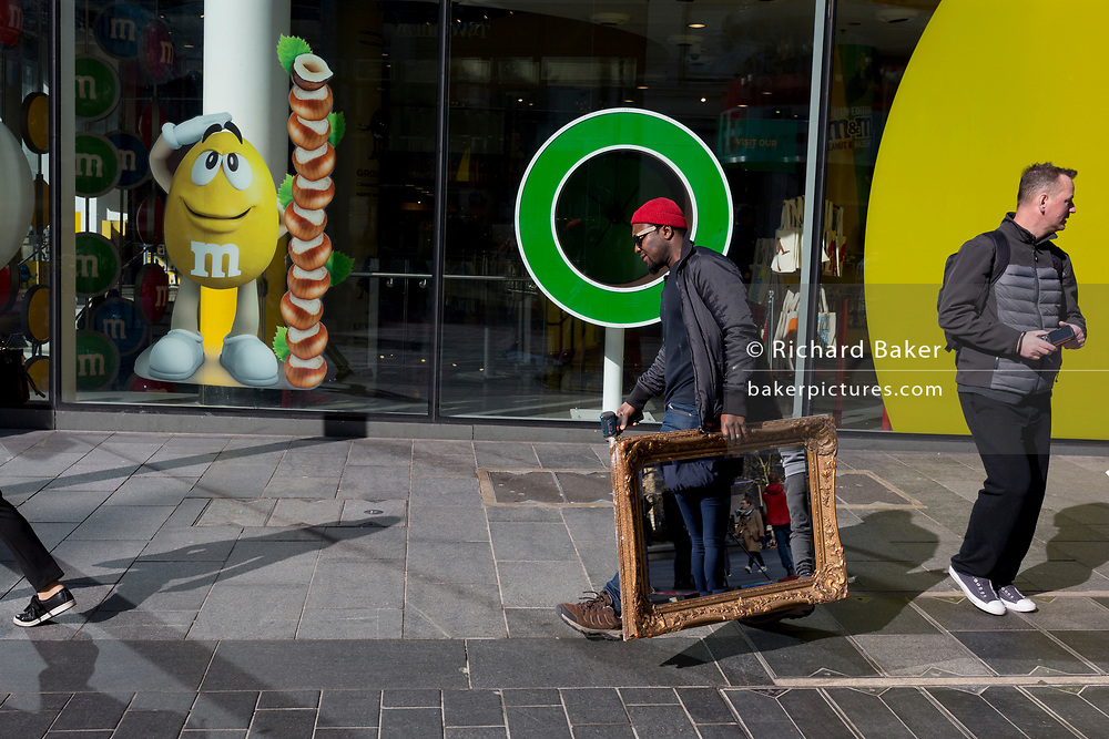Reflecting the legs of other pedestrians, a workman carries a guilded mirror and a Bosch hand tool past the cartoon characters of the M&M's World shop in Leicester Square, on 12th March 2020, in London, England.