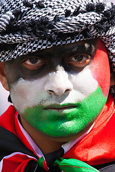 London, August 9th 2014. His face painted in the colours of the Palestinian flag, one of up to 150,000 protesters marches towards a Hyde Park rally.