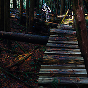 Owen Dudley rides across the skinnies on the Sonar trail in Bellingham Washington.