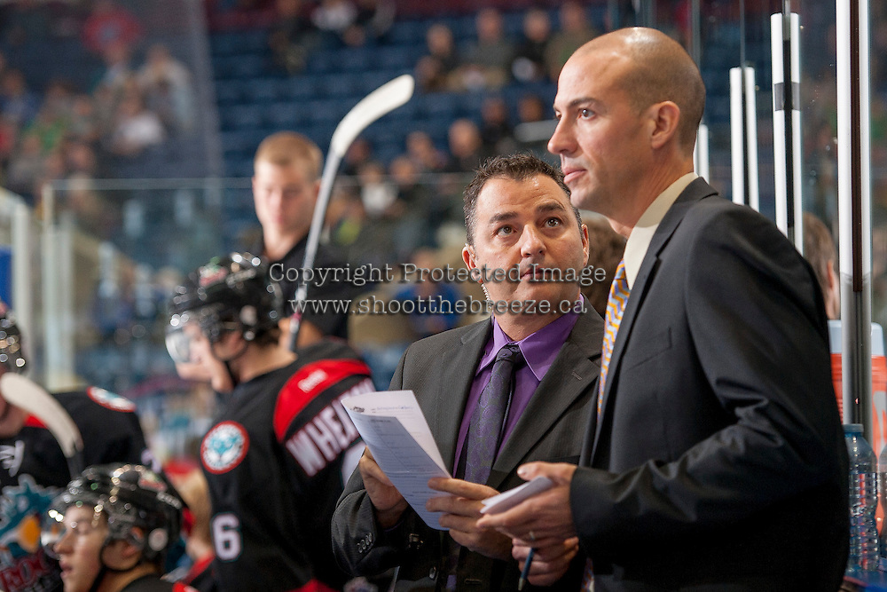 KELOWNA, CANADA - OCTOBER 22: Dan Lambert and Ryan Huska, coaches of the Kelowna Rockets, discuss a play on the bench opposite the Calgary Flames on October 22, 2013 at Prospera Place in Kelowna, British Columbia, Canada.   (Photo by Marissa Baecker/Shoot the Breeze)  ***  Local Caption  ***