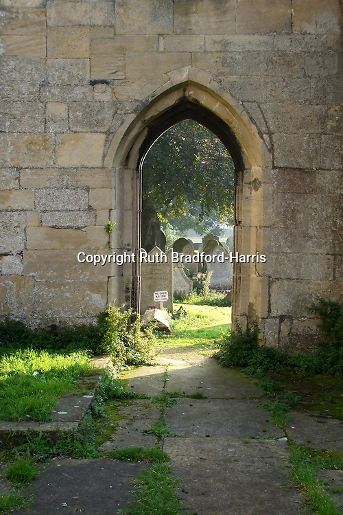 Early morning sun lights a misty churchyard, seen through a Gothic arch at Crowland Abbey, Lincolnshire.<br />