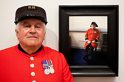© Licensed to London News Pictures. 20/06/2012. LONDON, UK. Tom Mullaney, a Chelsea Pensioner, stands next to his portrait painted by artist Louise Pragnell entitled 'Tom, Waiting', hung as one of the featured works at this years BP Portrait Award.  The annual British Petroleum sponsored event runs from the 21st of June to the 23rd of September and highlights the work of portrait artists working in a variety of styles and techniques . Photo credit: Matt Cetti-Roberts/LNP