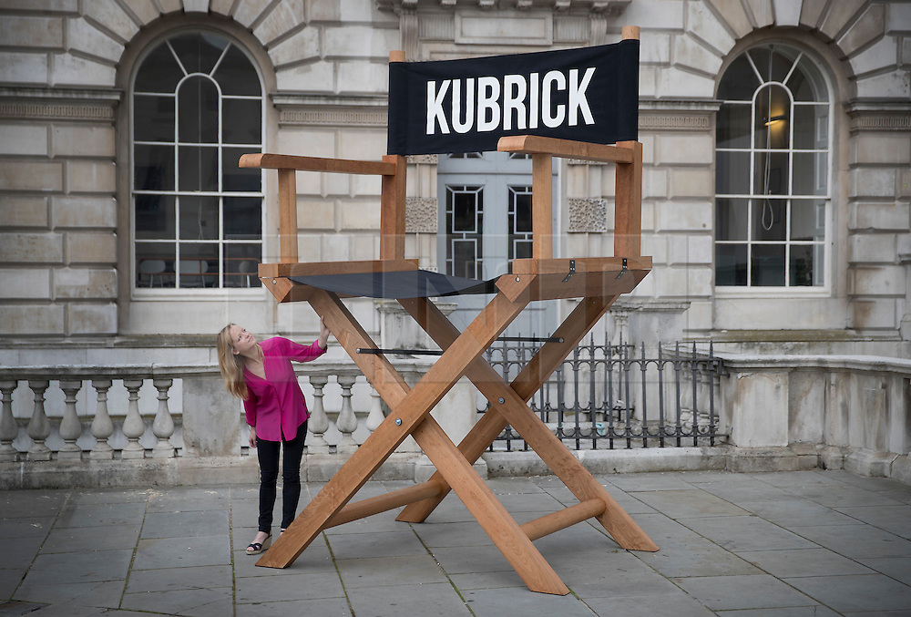 © Licensed to London News Pictures.  A Somerset House staff member looks up at an oversized director's chair by American artist Nancy Fouts, part of the exhibition Daydreaming with Stanley Kubrick in partnership with Canon at Somerset House in London. The show opens on July 6, 2016 and runs until August 24, 2016.  The exhibition features 50 works inspired by the legendary film director from a host of contemporary artists, musicians and filmmakers. London, UK.   Photo credit: Peter Macdiarmid/LNP