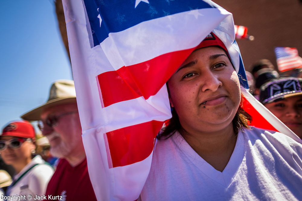 05 OCTOBER 2013 - PHOENIX, ARIZONA: A woman uses an American flag for shade during an immigration march in Phoenix. More than 1,000 people marched through downtown Phoenix Saturday to demonstrate for the DREAM Act and immigration reform. It was a part of the National Day of Dignity and Respect organized by the Action Network.  PHOTO BY JACK KURTZ