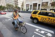 In San Francisco rijdt een fietser langs het autoverkeer door het centrum. De Amerikaanse stad San Francisco aan de westkust is een van de grootste steden in Amerika en kenmerkt zich door de steile heuvels in de stad. <br /> <br /> A cyclist in San Francisco. The US city of San Francisco on the west coast is one of the largest cities in America and is characterized by the steep hills in the city.