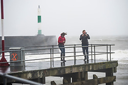 © Licensed to London News Pictures. 16/03/2019. Aberystwyth, UK. People struggle to walk as Storm Hannah brings huge waves crashing into the harbour lighthouse and sea defences on an extremely wet and windy day in Aberystwyth Wales.  Gusts of over 50mph are forecast to impact parts of the north and west of the country today as the period of very unsettled weather  continues to dominate the UK. Photo credit: Keith Morris/LNP