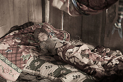 A Hmong boy lies sleeping in bed atop handmade quilts, Than Uyen area, Lai Chau, Vietnam, Southeast Asia