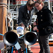 Preparations of the Fog Horn Requiem a few hours before the concert is about to start. Last minute installations and adjustments in the workshop and on the ships participating with remote controled horns. A REQUIEM FOR THE FOGHORN, PERFORMED BY SEVENTY FIVE BRASS PLAYERS, A FOGHORN AND AN ARMADA OF SHIPS<br /> A project by Danish artist, Lise Autogena, in collaboration with Joshua Portway and composer Orlando Gough. The performance took place by Souter Light House by South Shields, UK with 8-10.000 spectators and more than 50 ships off-shore.
