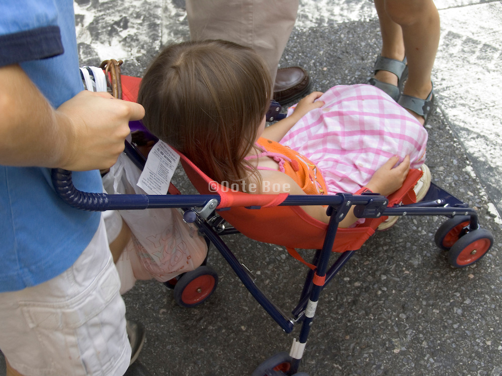 young girl sitting in a stroller with family members around her