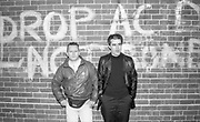Lee and Chrissy from Madness, posing against 'Drop acid not bombs' graffiti, UK, 1980s.