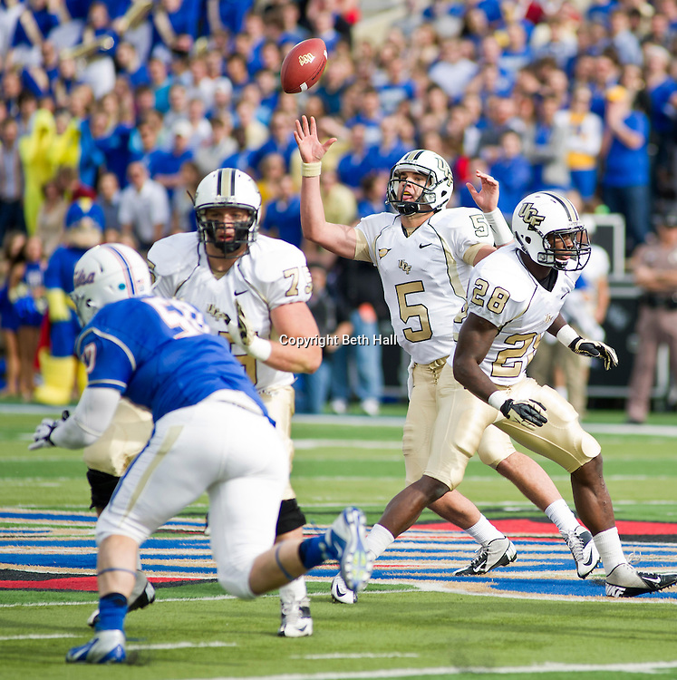 Dec 1, 2012; Tulsa, OK, USA; University of Central Florida Knights quarterback Blake Bortles (5) reaches to recover a bad snap as running back Latavius Murray (28) and offensive lineman Phil Smith (75) block and Tulsa Hurricanes defensive end Jared St. John (50) pursues during the first half of a game at Skelly Field at H.A. Chapman Stadium. Mandatory Credit: Beth Hall-US PRESSWIRE
