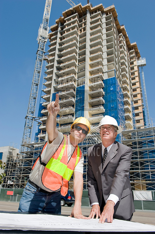Building developer supervising construction of a hirise with the construction foreman at the job site