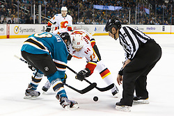 Feb 8, 2012; San Jose, CA, USA; NHL linesman Tony Sericolo (84) drops the puck on a face off to San Jose Sharks center Joe Pavelski (8) and Calgary Flames center Olli Jokinen (13) during the second period at HP Pavilion. Calgary defeated San Jose 4-3. Mandatory Credit: Jason O. Watson-US PRESSWIRE