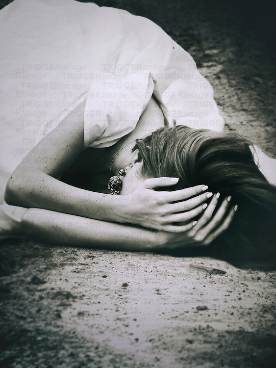 A woman in a white bridal gown, laying on the ground with her head in hands in a dramatic expression.