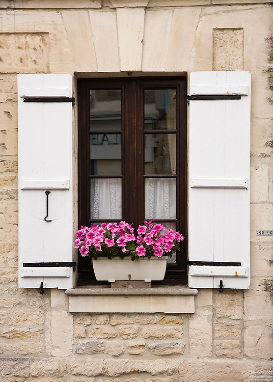 Close-up image of a window with colorful flowers common at most communities in France.