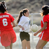 100114  Adron Gardner/Independent<br /> <br /> Navajo Prep Eagle Sydni Sky Ancira (2) holds a pass between two Holbrook Roadrunners at the Gallup Sports Complex Wednesday.