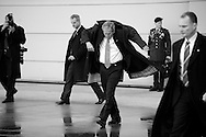 U.S. President George W. Bush puts on his raincoat as he departs a final visit with Air Force One crew members, called the Presidential Airlift Group, at Andrews Air Force Base, Maryland.