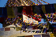 The ever-present eyes of the stupa at Boudhanath, peer through a caleidoscope of multi-colored prayer flags during the Tibetan New Year in Kathmandu, Nepal.