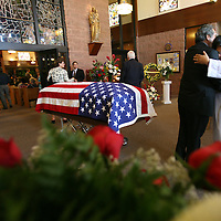 Deacon Fernando Heredia hugs a mourner in the vestibule of Sacred Heart Catholic Church in Palm Desert on Friday, July 31, 2009, next to the flag-draped casket of church parishoner Carlos Ortega before Ortega's funeral mass. Ortega retired in December 2008 from his post as Palm Desert's city manager after more than 30 years of service to the city. He passed away on July 21, 2009. Crystal Chatham, The Desert Sun