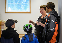Phyllis Sage explains to Nishan Weerasinghe (right) and his sons Jacob (right) and Alex the restoration process of the fire hall located on the grounds of historic Fort William H. Seward, located in Haines, Alaska.<br /> <br /> The fire hall was restored over a two-year period by owners Sage and Joanne Waterman who also own the fort&rsquo;s original guardhouse, now a bed and breakfast, located next door to the fire hall.<br /> <br /> After being absent from the historic Fort Seward skyline since approximately the 1930s, the 60-foot tower of the fort&rsquo;s fire hall has been restored to its original height. The building and tower, built around 1904 in Haines, Alaska, was shortened to approximately half its height in the 1930s for unknown reasons. The restoration included rebuilding a missing 35-foot section of the 60-foot tower whose purpose was to dry fire hoses. The tower restoration was completed by building its four sections on the ground and then hoisting those sections with a crane into place on top of each other.<br /> <br /> Through the years, the historic Fort Seward area, a former U.S. Army post, has been referred to as Fort William H. Seward, Chilkoot Barracks, and Port Chilkoot. The National Historic Landmarks listing record for the fort says that &quot;Fort Seward was the last of 11 military posts established in Alaska during the territory's gold rushes between 1897 and 1904. Founded for the purpose of preserving law and order among the gold seekers, the fort also provided a U.S. military presence in Alaska during boundary disputes with Canada. The only active military post in Alaska between 1925 and 1940, the fort was closed at the end of World War II.&rdquo; <br /> <br /> The bottom portion of the fire hall is being leased as commercial space. Due to fire code restrictions there is no public access to the upper portion of the tower.
