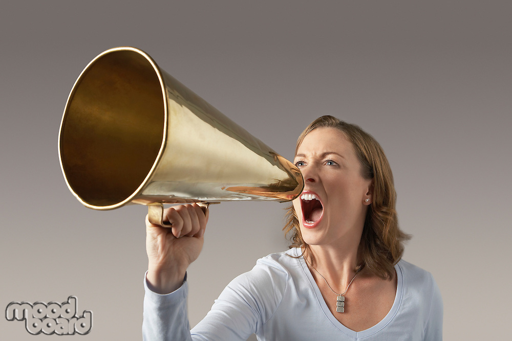 Angry Mid-adult woman shouting through megaphone