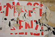 Political poster peeling on a wall in the northern Italian city of Trento.