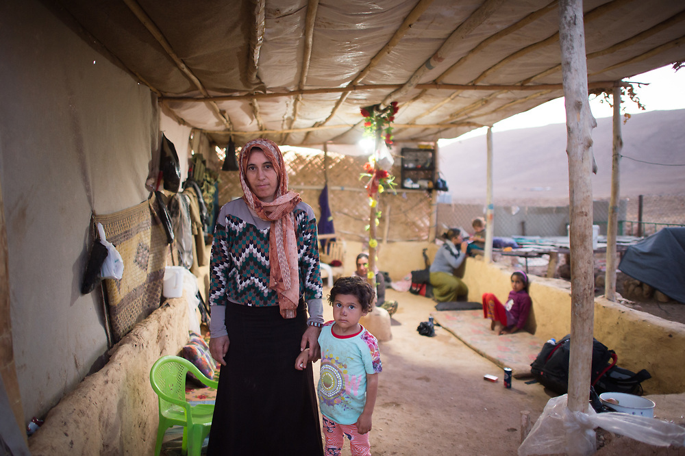 Ewaish* stands together with her daughter Mizgen* in front of her hut near Shingal City. ISIS kidnapped them in August 2014 and took them to Raqqa. Ewaish parents have been killed by ISIS when trying to flee and the remain of Ewaish's other ten year old daughter is unknown. Ewaish escaped her captors two weeks ago. She lives now with her husband and Mizgen in a provisional hut because her village is still in the hands of ISIS. (*names have been changed) Shingal (Sinjar), Iraq, August 27, 2015