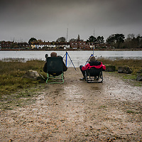 Two men sitting in chairs fishing on an estruary in Bosham West Sussex, England