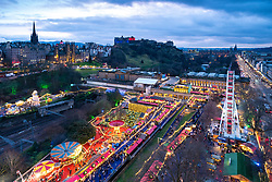 View of Edinburgh Christmas Market in west Princes Street gardens and skyline of the city towards the castle in Edinburgh, Scotland, UK