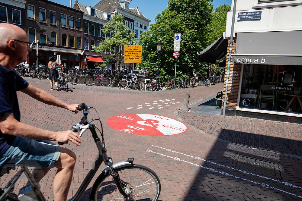 Een man slaat af vlak voor het nieuwe voetgangersgebied. In Utrecht worden fietsers gewezen op een andere route. Vanaf 1 mei mogen fietsers gedurende het grootste deel van de dag niet meer door een deel van het centrum fietsen. Het voetgangersgebied is fors uitgebreid.<br /> <br /> A big painted sign on the road suggest cyclists another route to ride at the city center in Utrecht. A part of the center is closed for cyclists for the main part of the day.