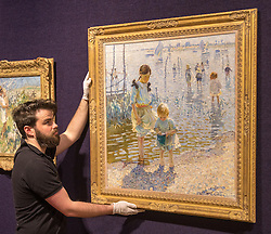 Bonhams, London, February 22nd 2017. Bonhams in London hold a press preview ahead of their 19th century paintings sale, featuring numerous valuable works including:<br /> • 'Children by the shore' by Dorothea Sharp, valued at £60,000-80,000<br /> • Barcas y pescaadores, Playa de Valencia by Joaquin Sorolla £60,000-80,000<br /> • When the Boats Come In by Walter Osborne valued at £100,000-150,000<br /> • A Solicitation by Lawrence Alma-Tadema which is expected to fetch between £30,000-50,000<br /> PICTURED: A gallery porter adjusts Children by the shore' by Dorothea Sharp