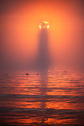 © Licensed to London News Pictures. 07/08/2020. Scarborough UK. Scarborough lighthouse is shrouded with sea fog as the sun rises this morning on the Yorkshire coast. Photo credit: Andrew McCaren/LNP