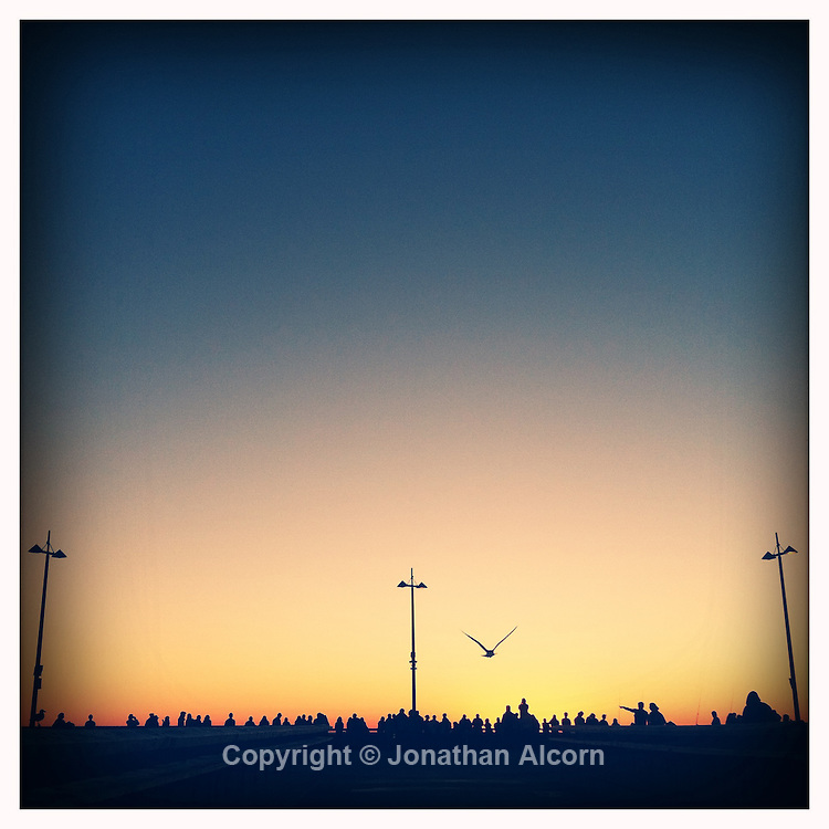 A crowd gather on the Venice Pier to watch the setting Sun on December 28, 2011