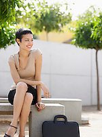 Smiling Businesswoman sitting on bench in plaza