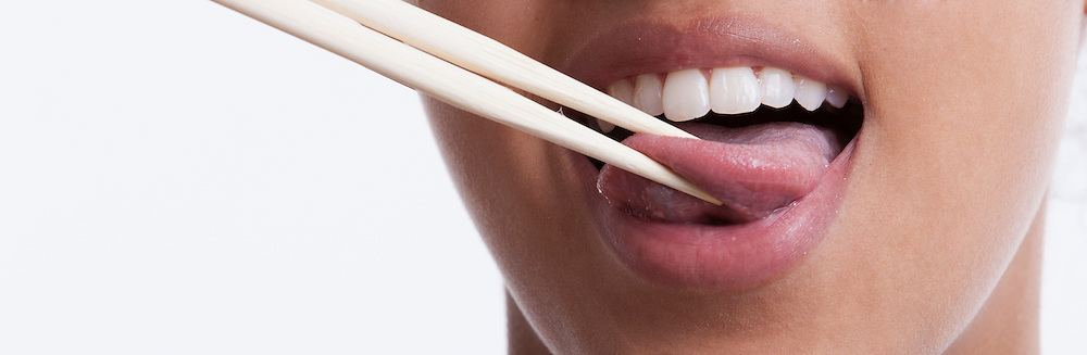 Playful young woman with chopsticks sticking out tongue against white background