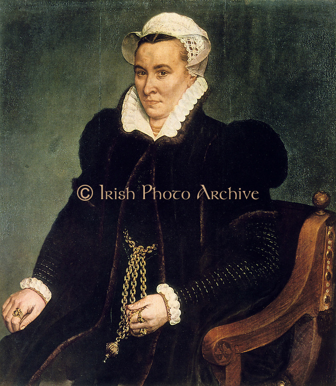 Portrait of a Woman: oil on wood. Francis Pourbus the Elder (1545-1581) Flemish painter.  Seated woman in velvet gown, a ruff and white cap. Round her neck  and wrists are goldchains. She holds the end of a heavy gold chain with a pendant and on her hands are gold rings set with precious stones.