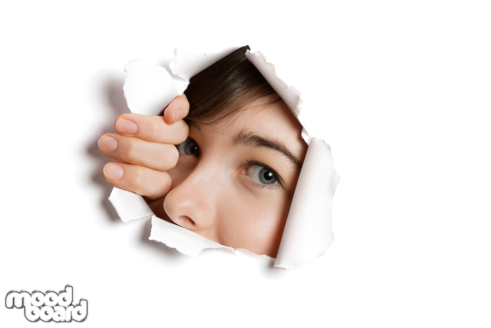 Portrait of a young Middle eastern woman peeking from ripped white paper hole