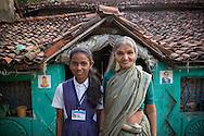 Saloni tillsammans med sin farmor Saru Ganvir, framför deras hem med Buddha och Dr Ambedkar på husfasaden. Bandhara, Maharashtra, Indien