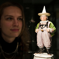 LONDON, ENGLAND - NOVEMBER 24:   Nette Megens, a Bonhams porcelain specialist, poses with a Meissen figure of the Court Jester Joseph Frolich circa 1752 on November 24, 2009 in London, England.  Bonhams will hold three separatee sales for the Hoffmaister Collection of Meissen porcelains, the first will be on November 25, 2009<br />