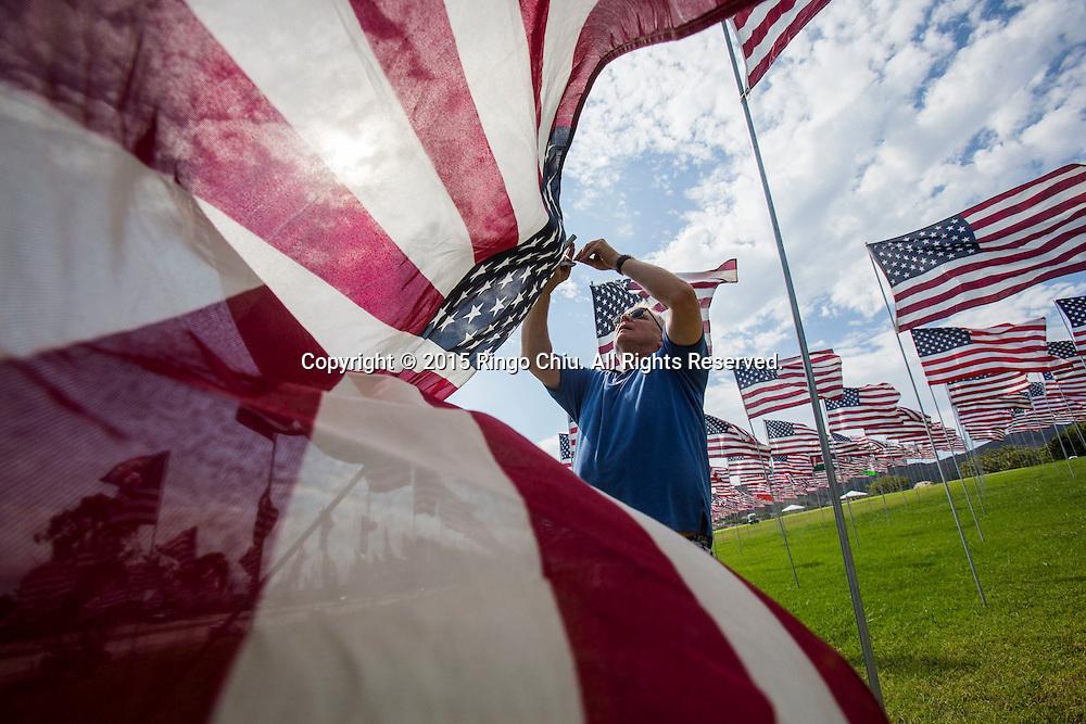 9月10日,在美国加利福尼亚州洛杉矶的马里布,一名志愿者竖起旗帜。当天,在美国&ldquo;9&middot;11&rdquo;事件十四周年前夕,佩珀代因大学的学生和教职员工在学校草坪上插起约3000面美国国旗,纪念&ldquo;9&middot;11&rdquo;事件遇难者。新华社发(赵汉荣摄)<br /> A volunteer  puts up one of 3,000 US flags are displayed at Pepperdine University to mark the 14th anniversary of the 9/11 terror attack, September 10, 2015 in Los Angeles, California, the United States. (Xinhua/Zhao Hanrong)Photo by Ringo Chiu/PHOTOFORMULA.com)