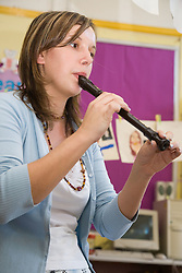 Teacher showing primary school pupils how to play the recorder in a music lesson at school,