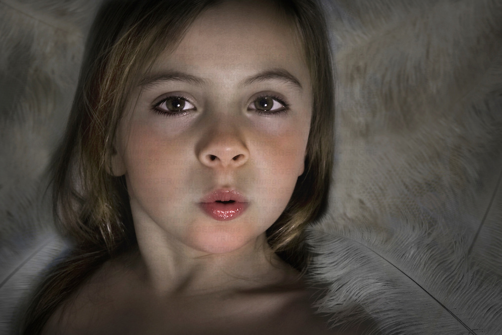 Young child with large eyes looking at the camera blowing a kiss, against a background of white feathers