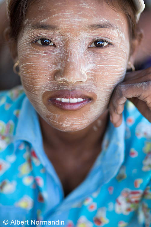 Portrait of young girl with Thanaka on her face, labourer, Pathein