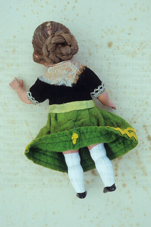 Vintage woman doll in lacy southern European dress and with plaited hair in bun lying face down on antique paper