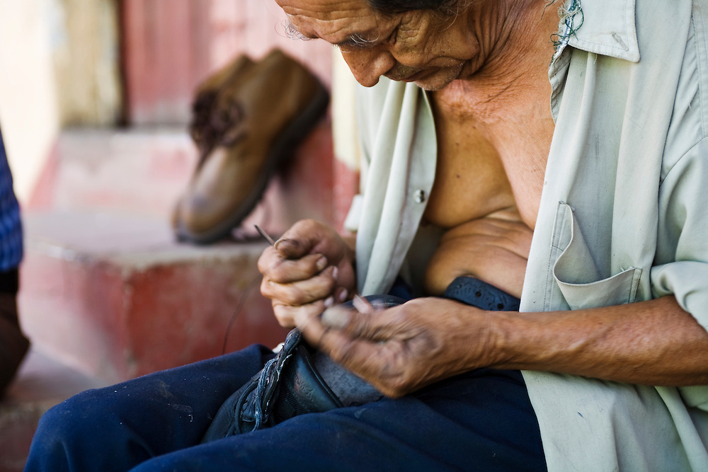 "A cobbler repairs a shoe in the market of Masatepe. Matatepe is one of the ""Los Pueblos Blancos, a series of towns on the central plateau of Nicaragua. It is located close to Granada, Nicaragua."