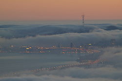 Fog rolls into the San Francisco bay during summer, covering the new bay bridge that's under construction.
